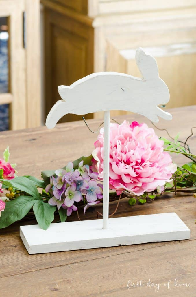 Leaping white wooden bunny on stand sitting on spring tablescape