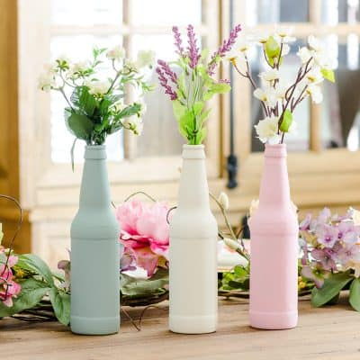 Painted bottles in pink, sage and cream using chalk paint with Dollar Tree flowers.