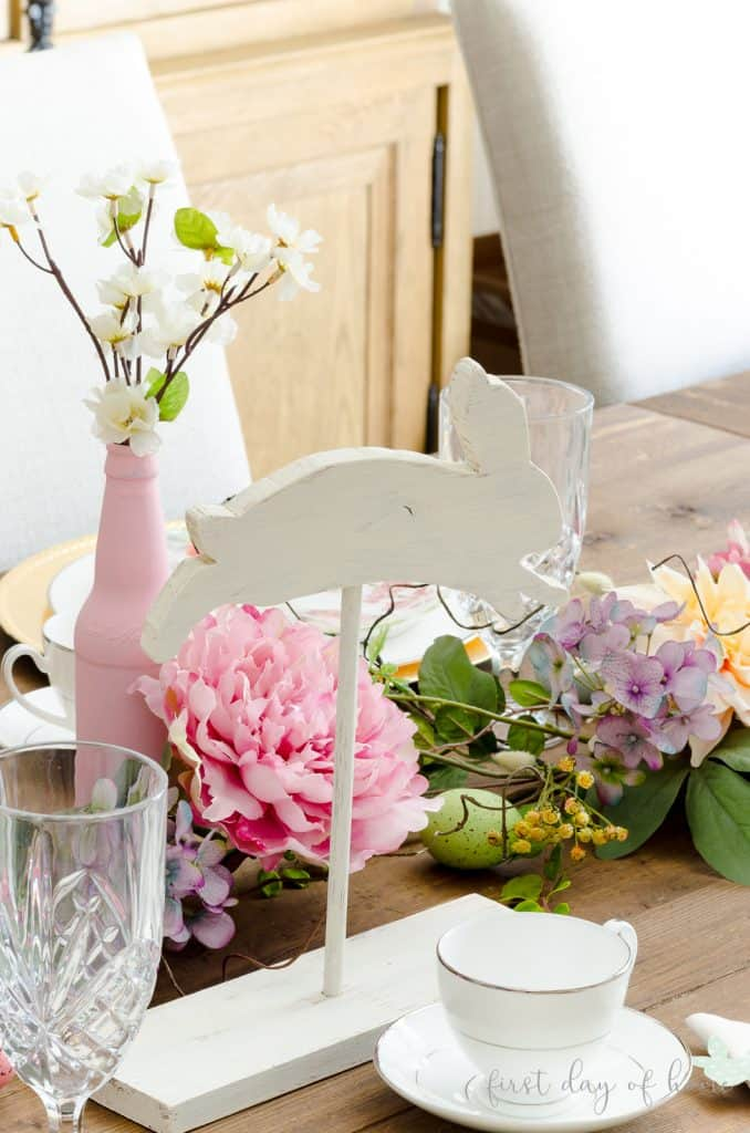 Spring tablescape with leaping wooden bunny and painted bottle vases