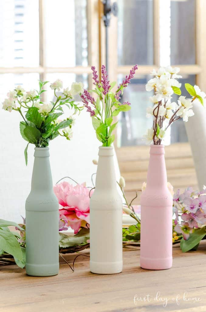 Painted bottles in blue, cream and pink made from upcycled beer bottles