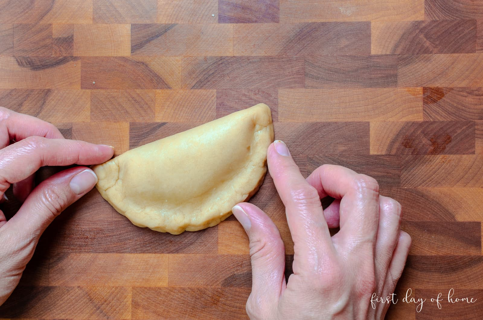 Sealing the edges of a pumpkin empanada made with authentic dough recipe