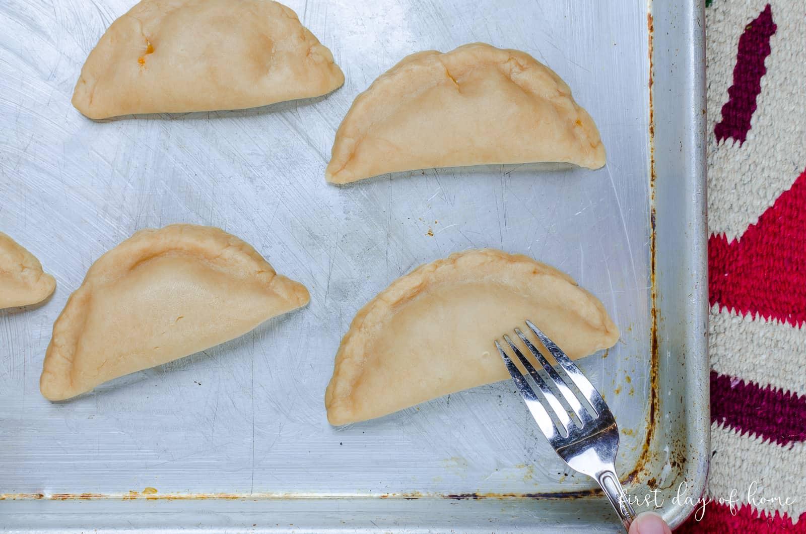 Poking holes in pumpkin empanada dough to create vent holes while baking
