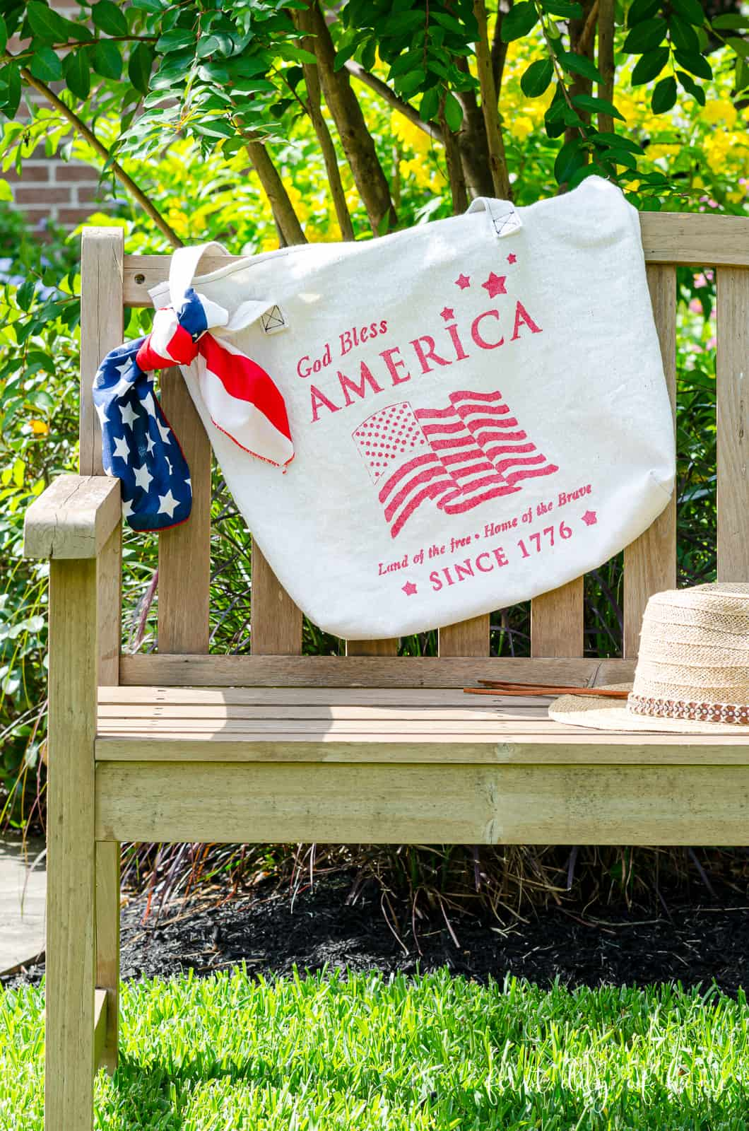 Stencil canvas bag with patriotic stencil and red, white and blue bandana on park bench