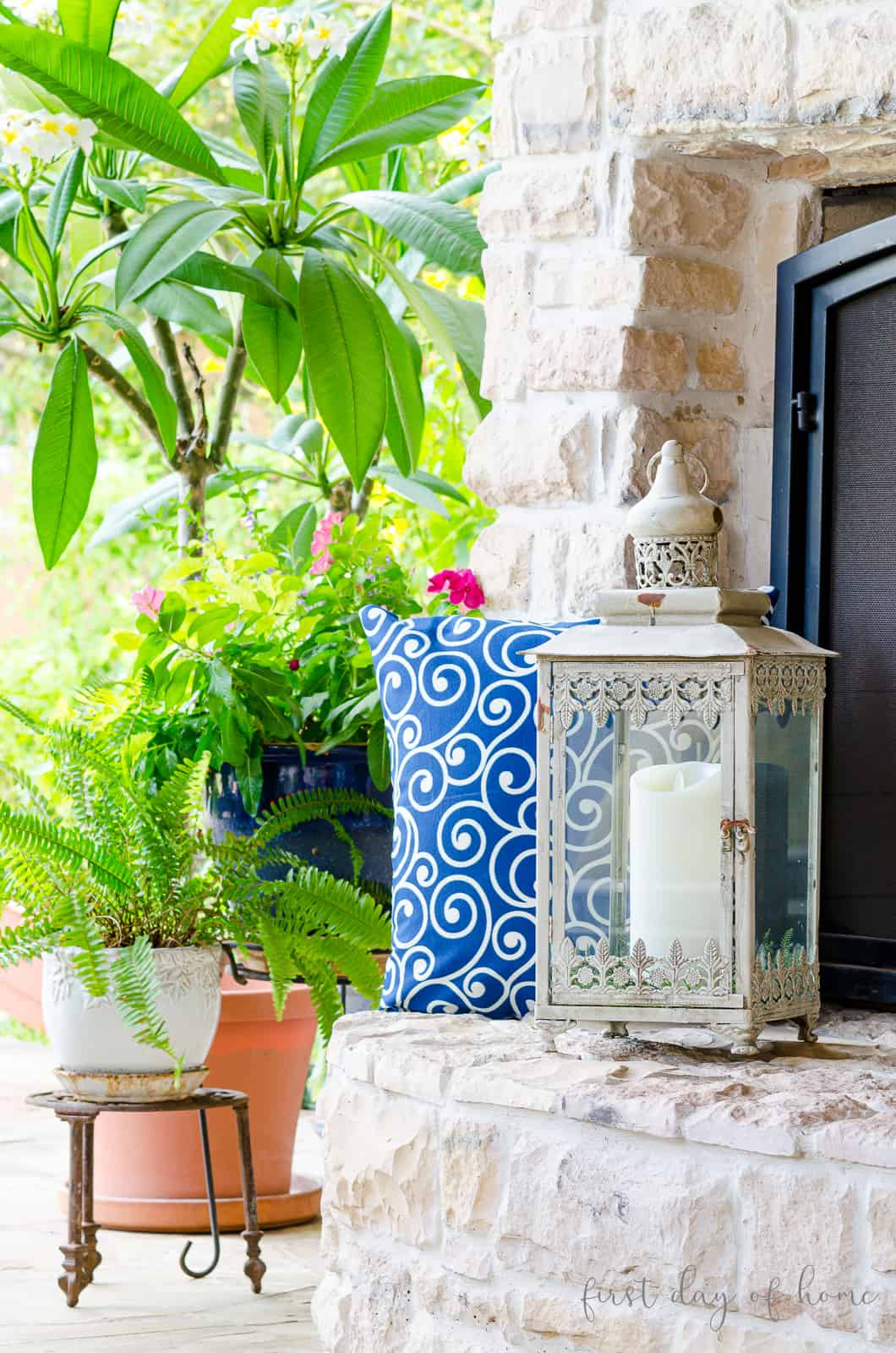 Neutral lantern on white stone hearth outdoors with plants and greenery in background