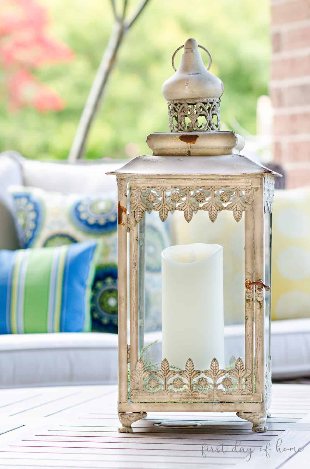 Moroccan style lantern with Moroccan pillows on patio furniture in background for outdoor lantern decorating ideas