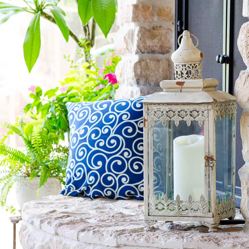 Lantern decor with pillar candle and vibrant blue pillow on outdoor patio