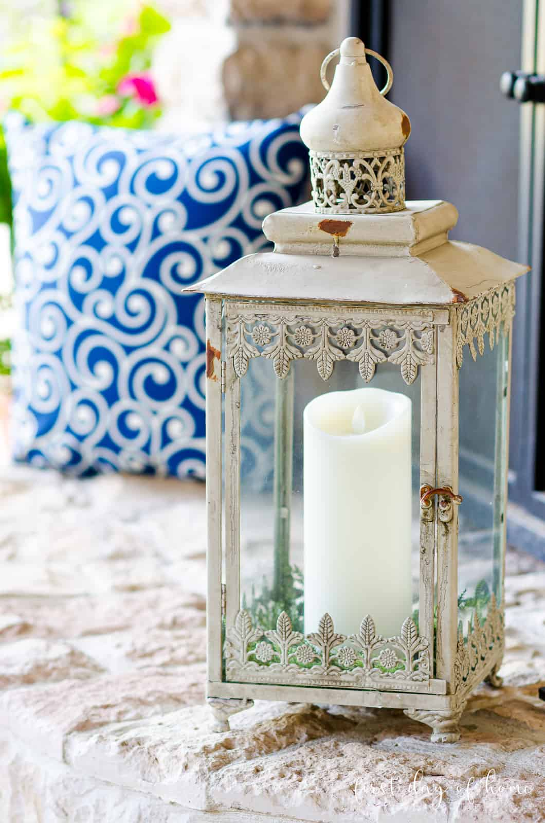 Neutral lantern with flameless pillar candle on outdoor fireplace with blue swirl pillow in background