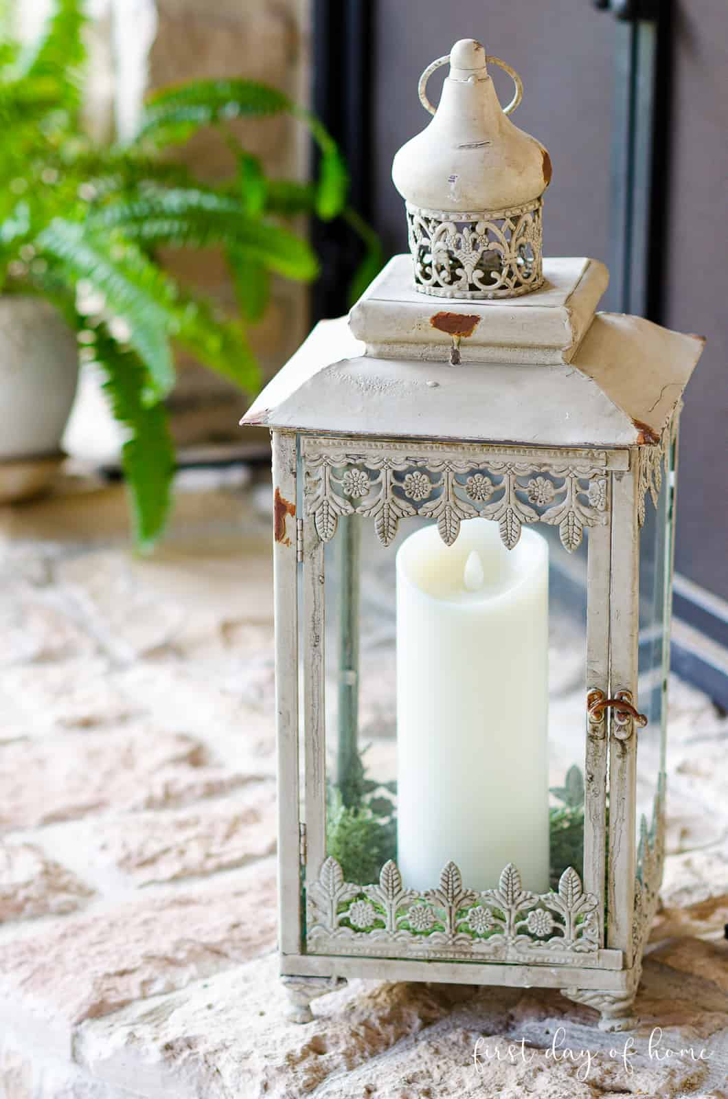 Greenery in moroccan lantern with pillar candle sitting on fireplace hearth outdoors