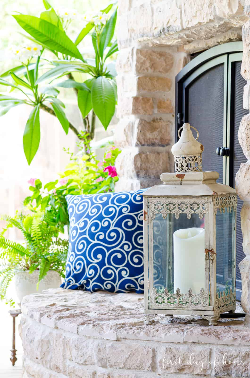 Neutral rustic Moroccan style lantern with pillar candle on outdoor patio with blue swirl pillow and plants in background
