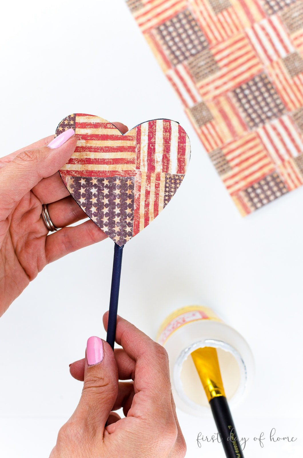Applying heart shaped scrapbook paper to wooden garden stakes with Mod Podge