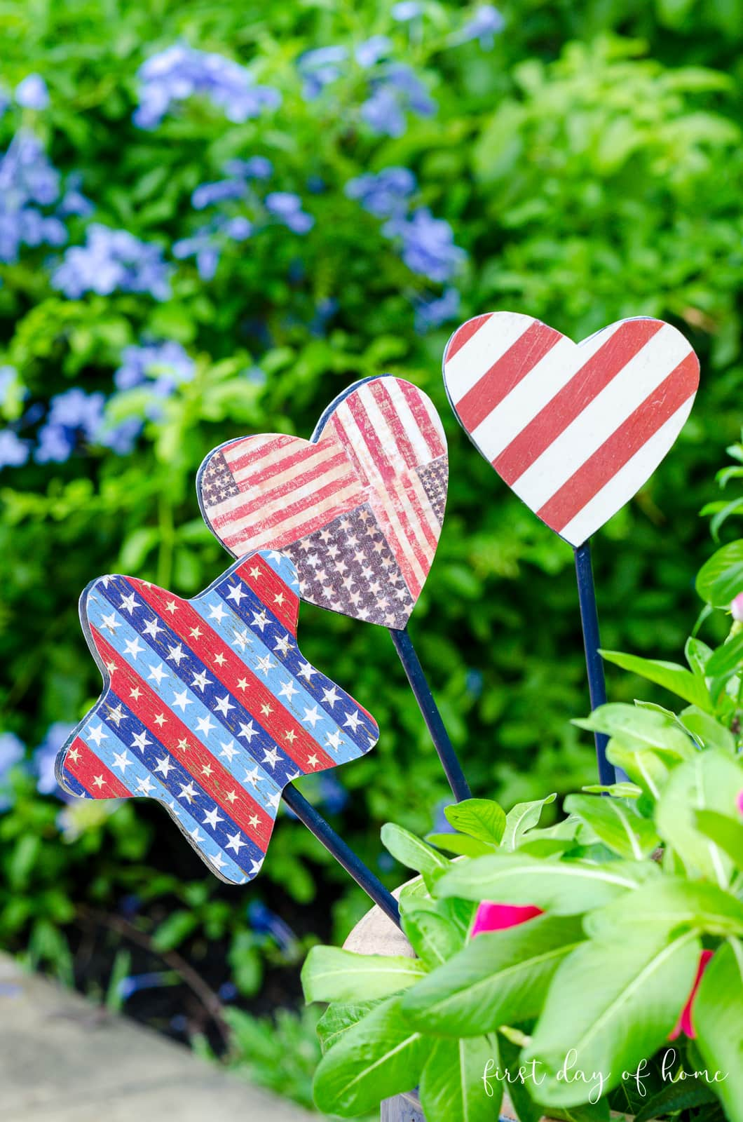 Trio of garden stakes with Americana patriotic theme sitting in flower pot - DIY tutorial