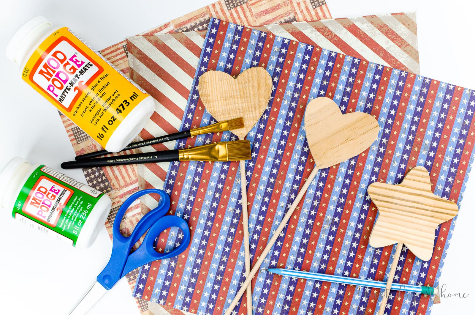 Supplies to make decorative stakes for a garden, including Mod Podge, scrapbook paper, scissors and paint brushes