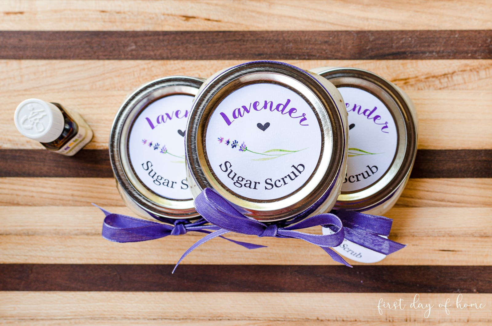 Trio of lavender sugar scrub recipe placed in short mason jars with printed labels on lids