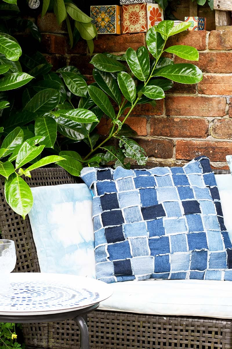 Upcycled denim woven pillow sitting on love seat
