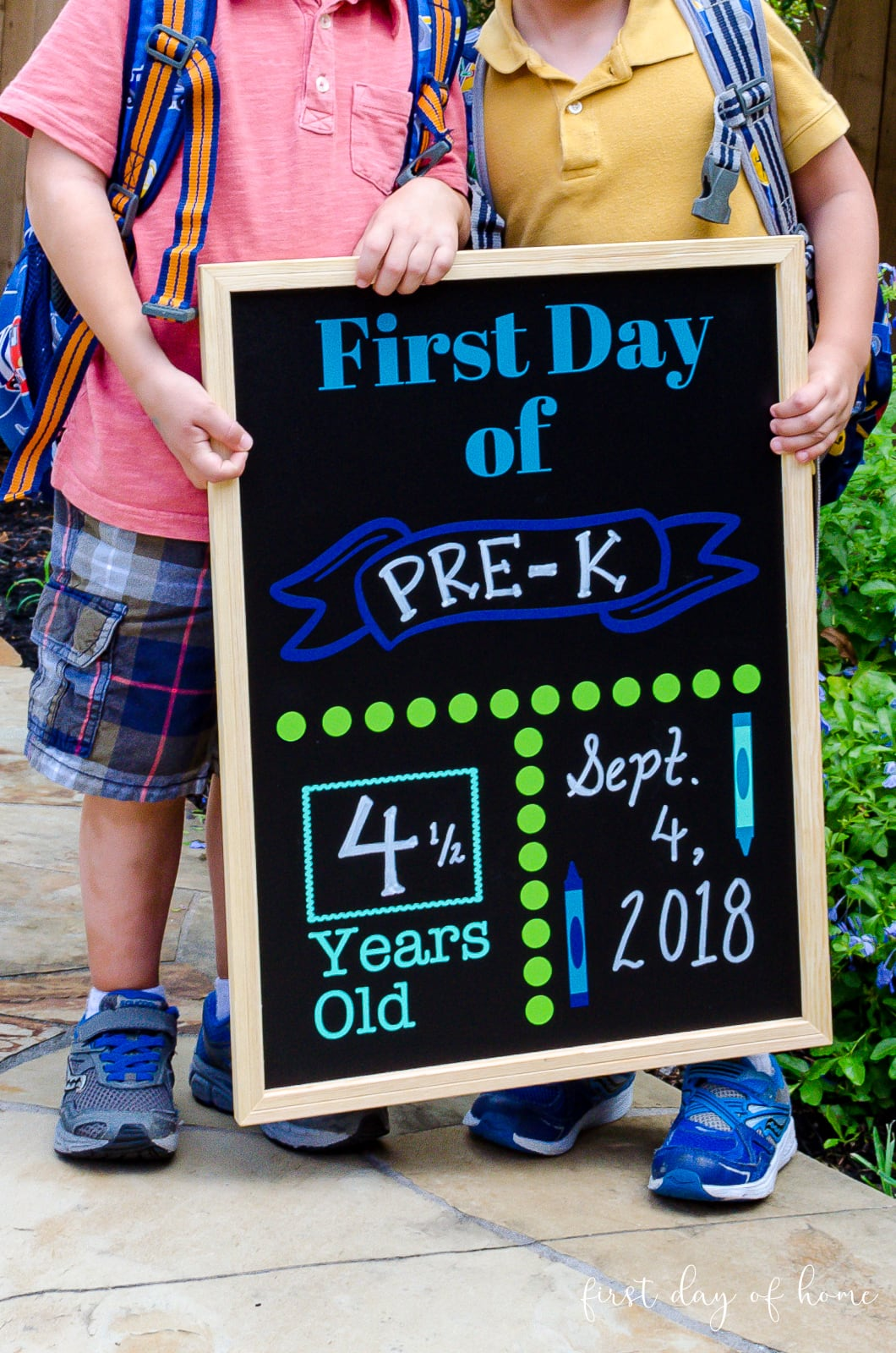 Back to school DIY chalkboard sign with boys holding it
