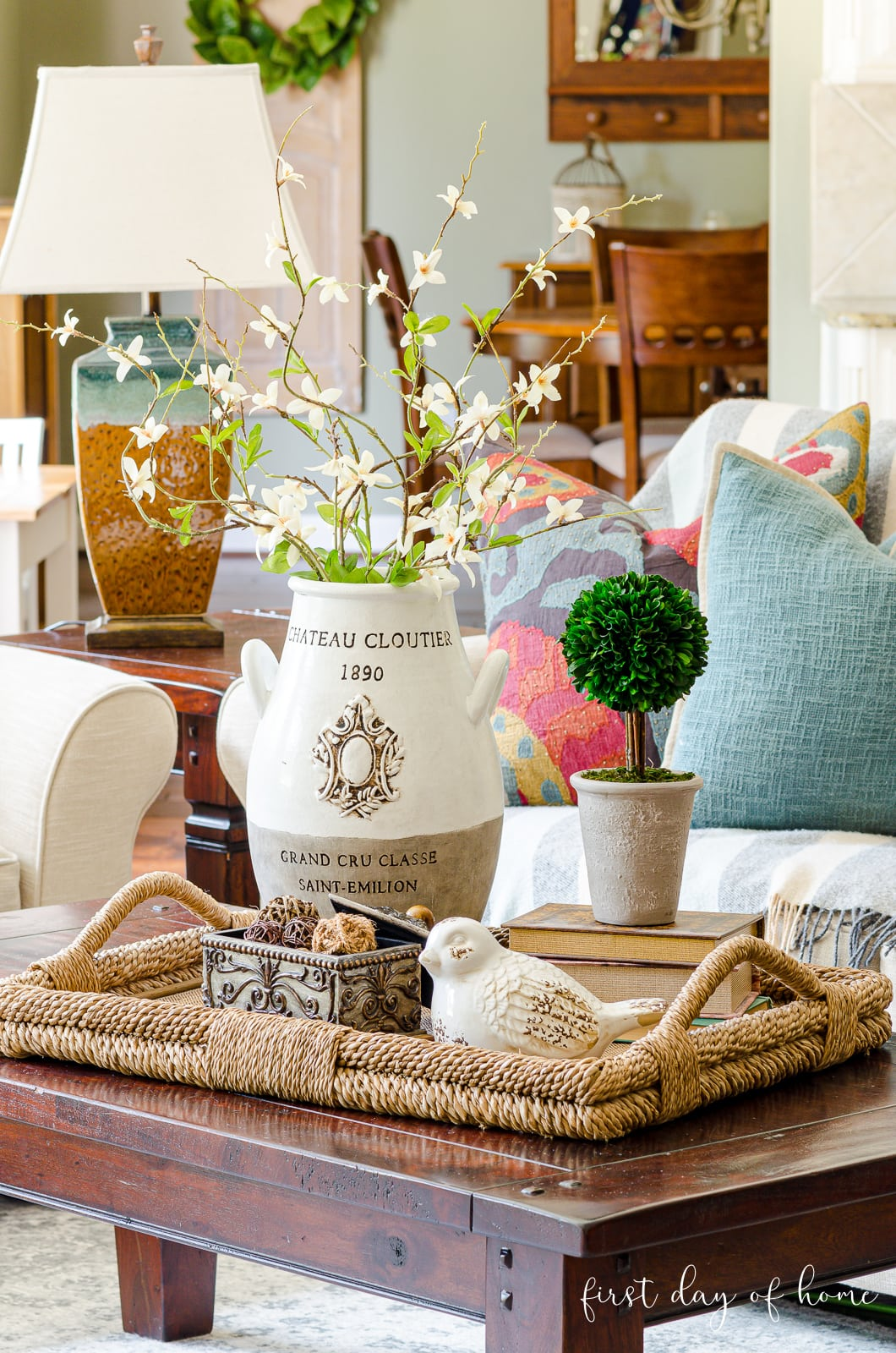 Coffee table decor ideas with french country urn, white ceramic decorative accent, books, boxwood topiary and rattan spheres