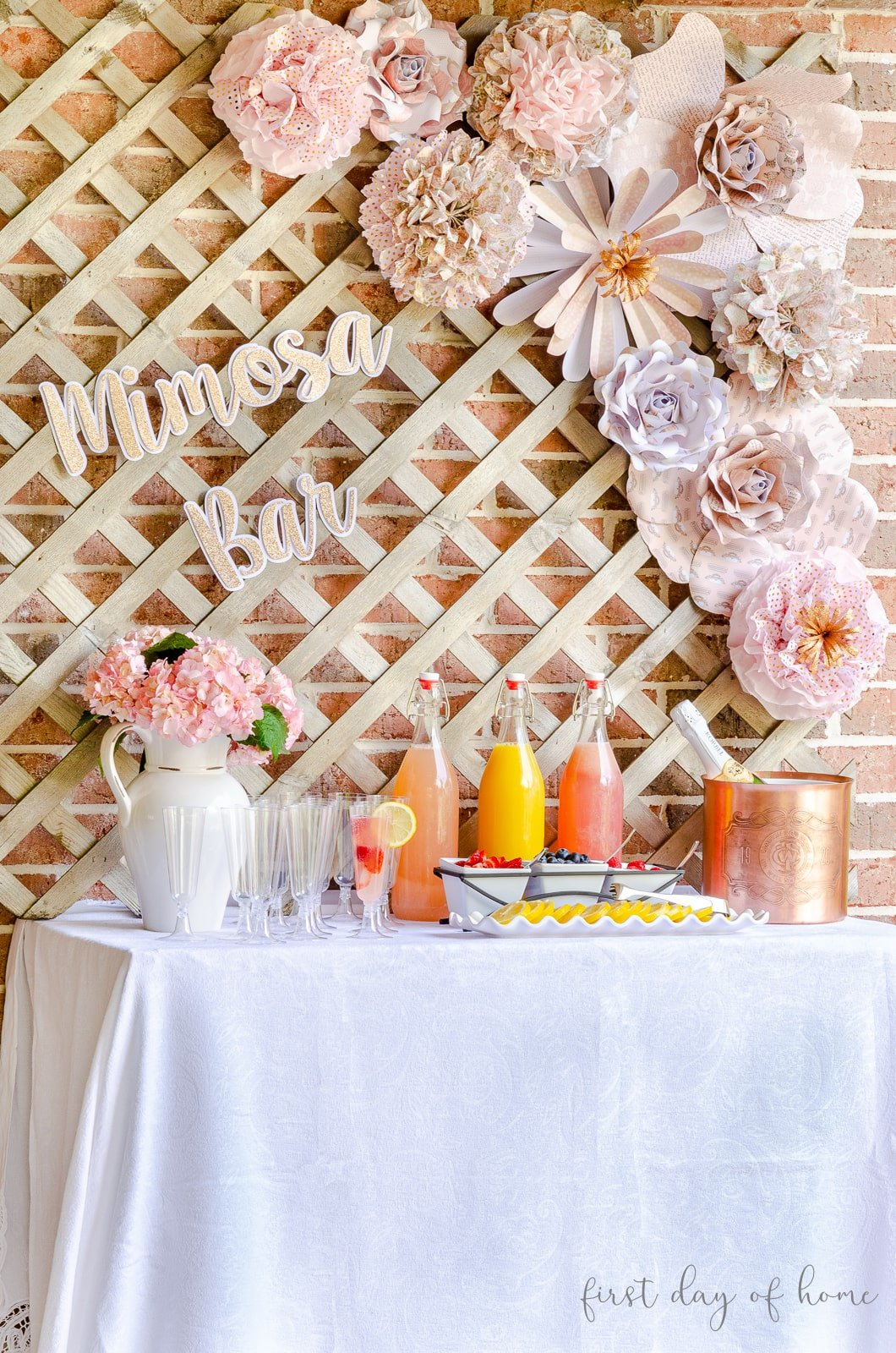Mimosa bar decor including paper flowers and DIY tissue paper pom poms, perfect for bridal shower