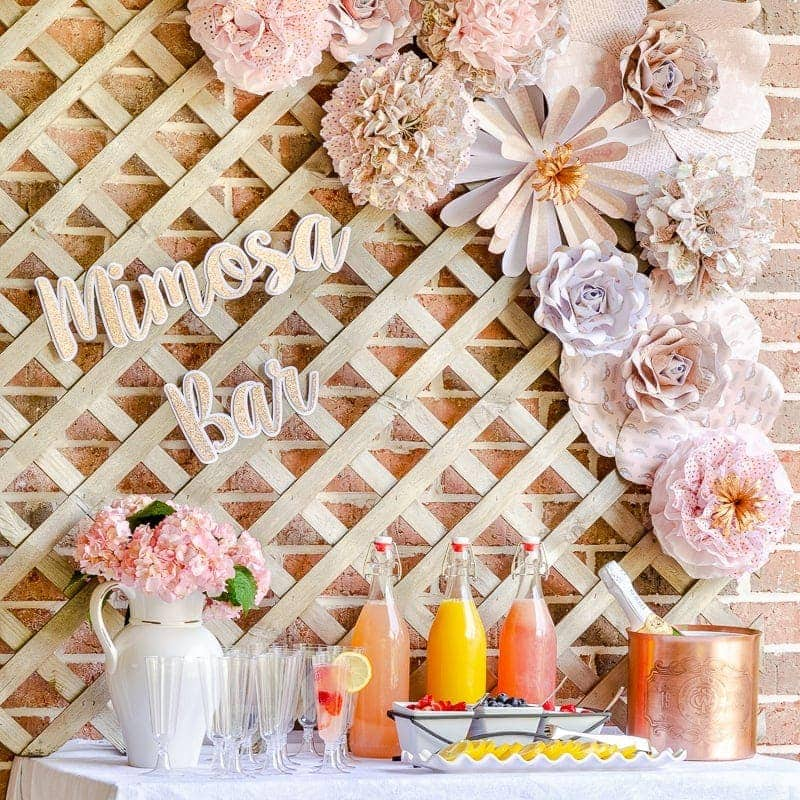 DIY mimosa bar with pink paper flowers and pom poms, fruit juices, champagne flutes and fresh flowers
