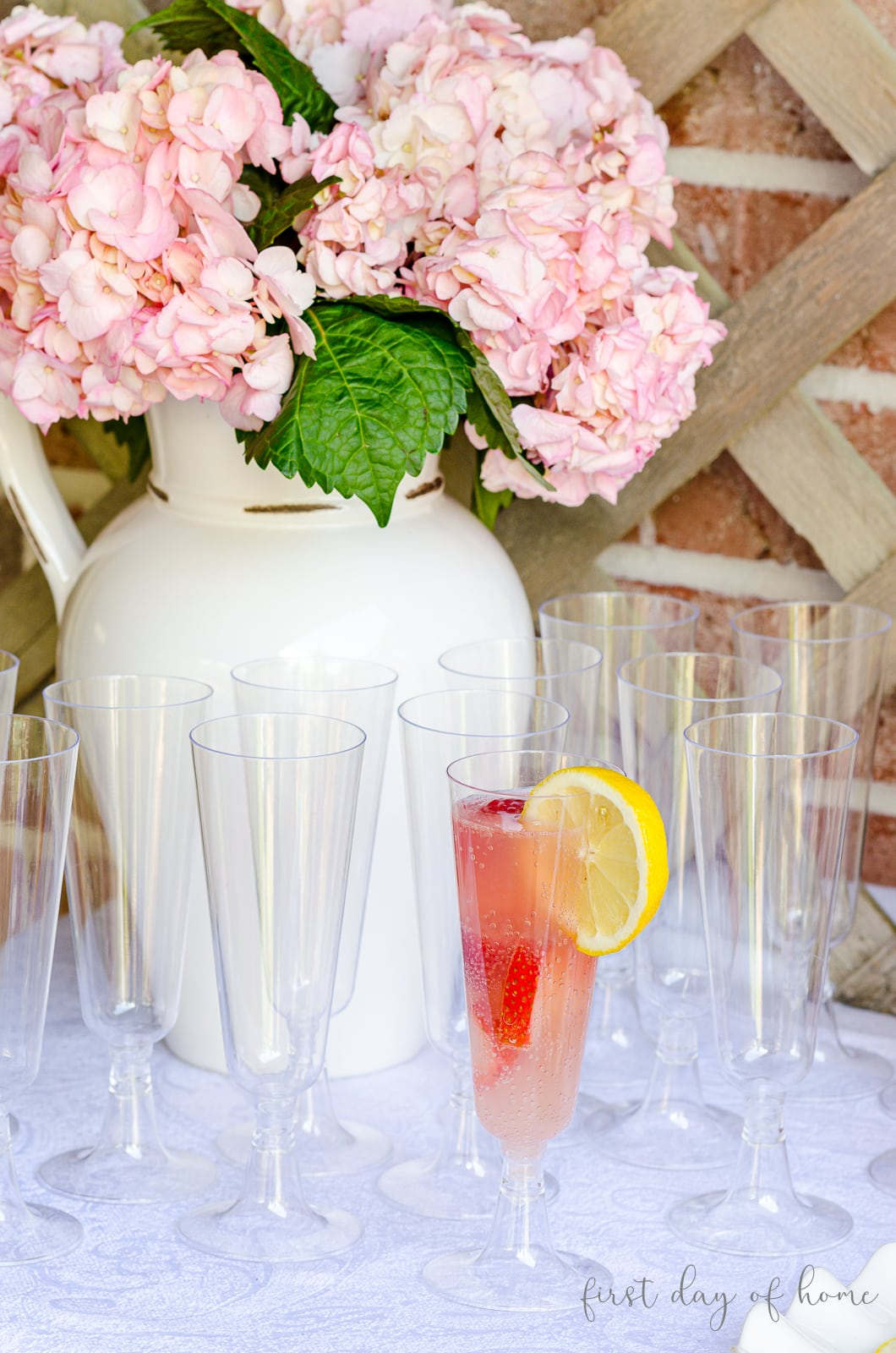 Pink mimosa drink with lemon wedge and pink hydrangea arrangement in background