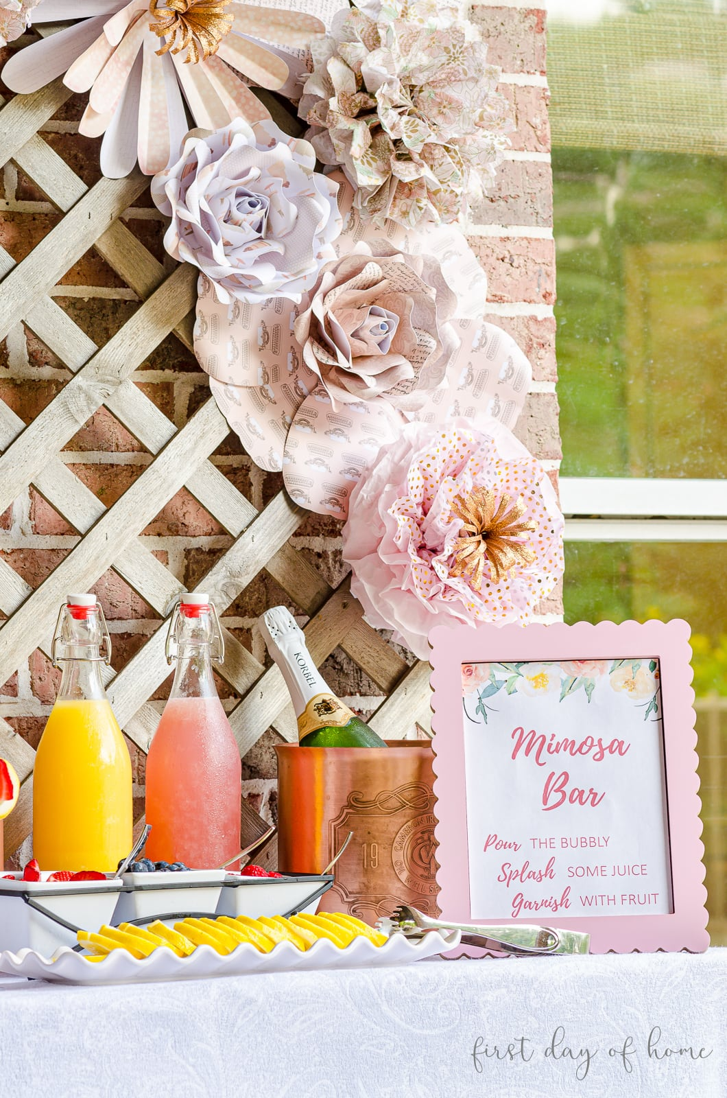 Mimosa bar sign on table in front of lattice with paper flowers