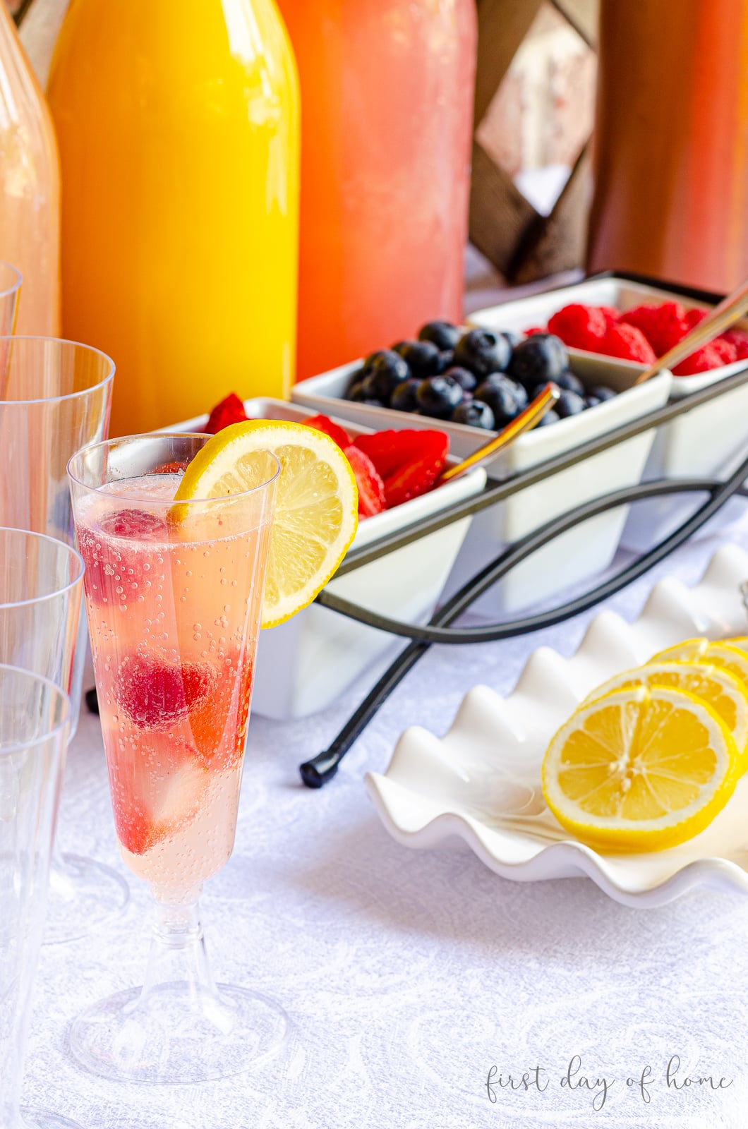 A champagne flute filled with juice and champagne with a lemon wedge in front of mimosa bar juices