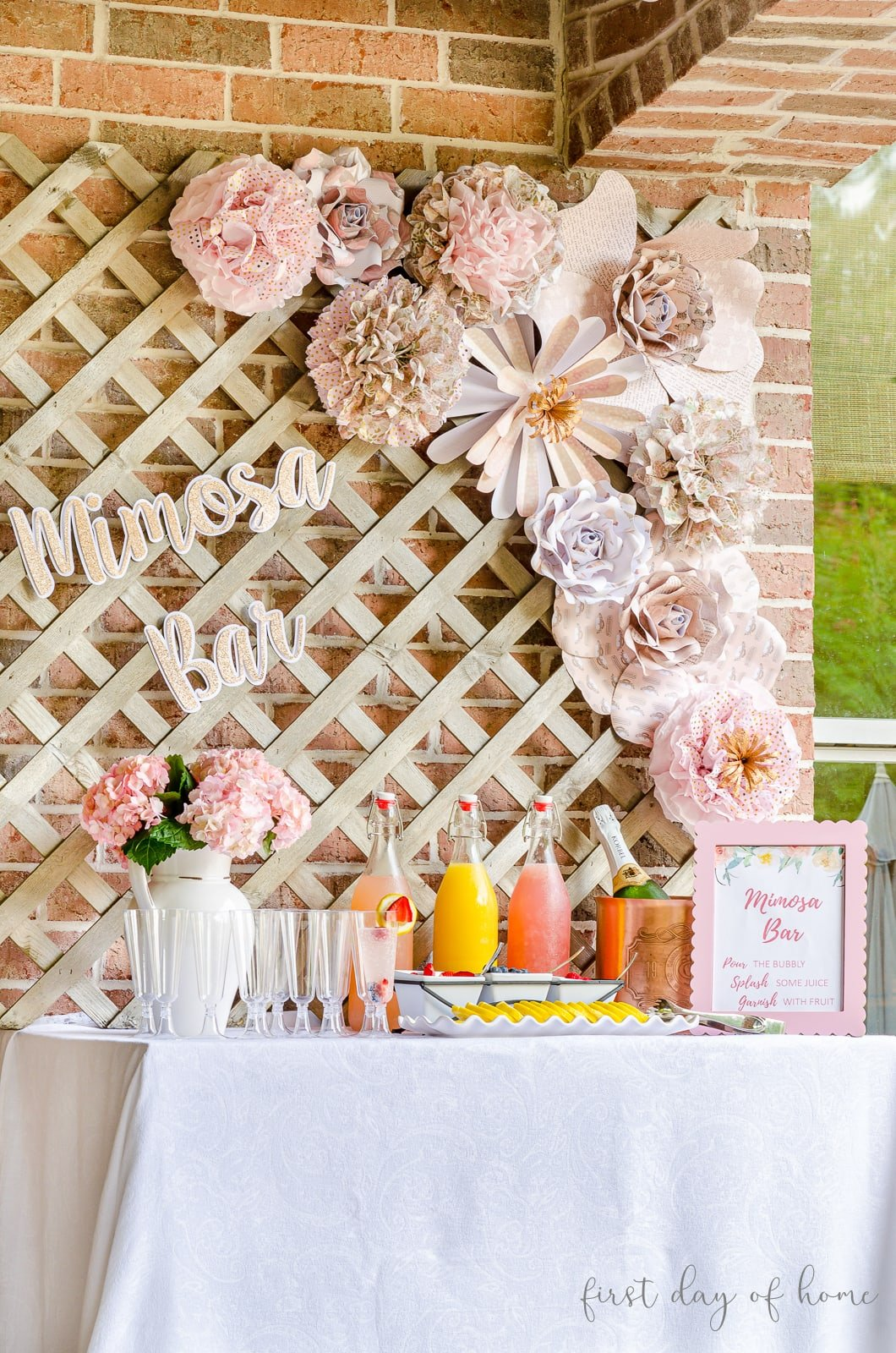 Mimosa bar sign with tissue paper pom poms and paper flowers on lattice behind DIY mimosa bar with fruit juices, champagne and garnishes