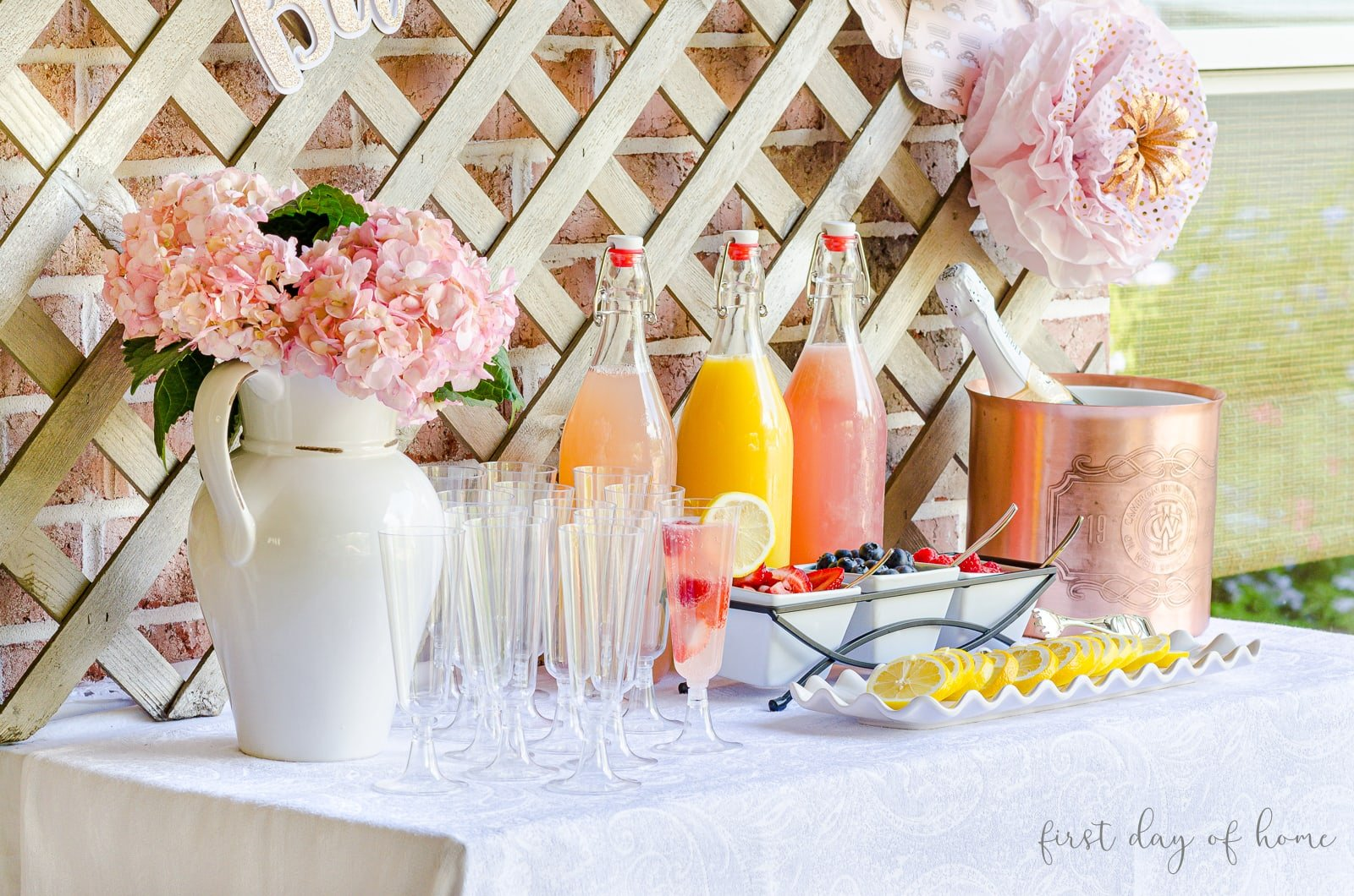 DIY mimosa bar with fresh hydrangea flowers, fruit juices, champagne and fruit garnishes