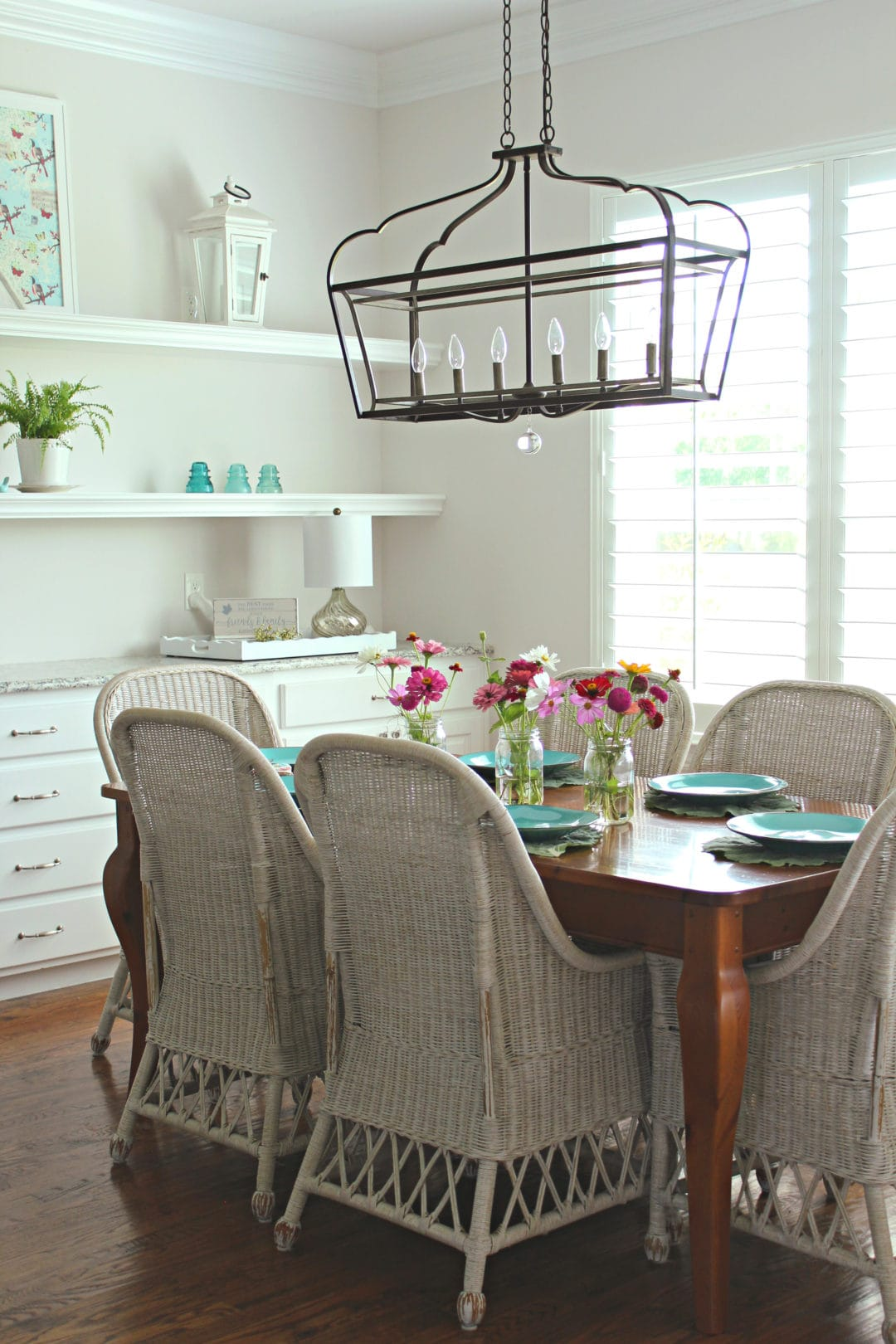 Poofing the Pillows summer home tour - breakfast area with wicker chairs and touches of farmhouse decor and shelving