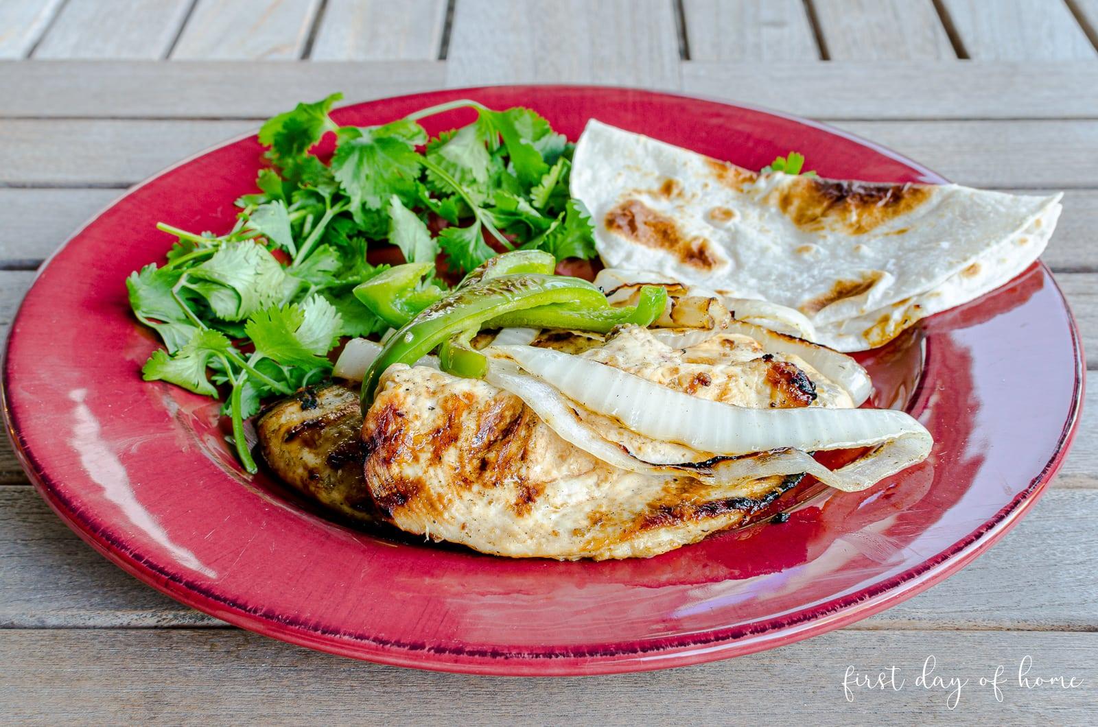 Authentic chicken fajita recipe served on plate with cilantrol garnish and flour tortilla