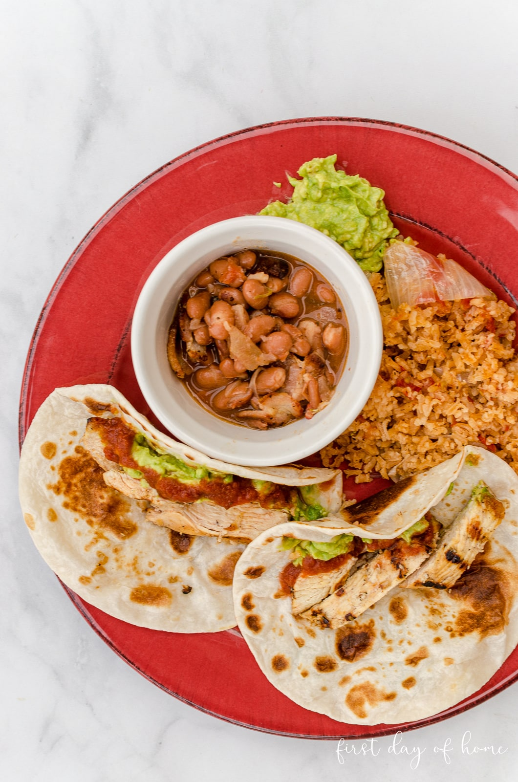 Chicken fajitas tacos served with Spanish rice and charro beans