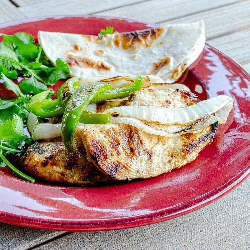 Grilled chicken fajitas on plate with tortilla and cilantro