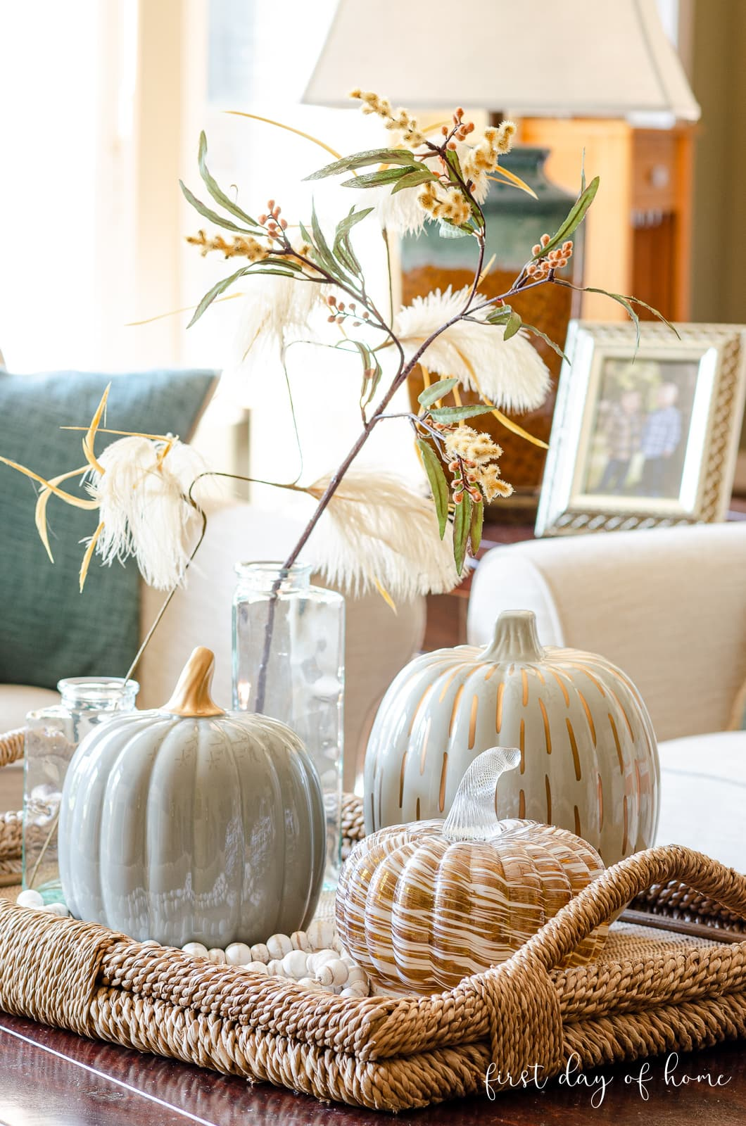 Fall home tour of living room with fall coffee table decor using ceramic pumpkins and faux florals in wicker tray