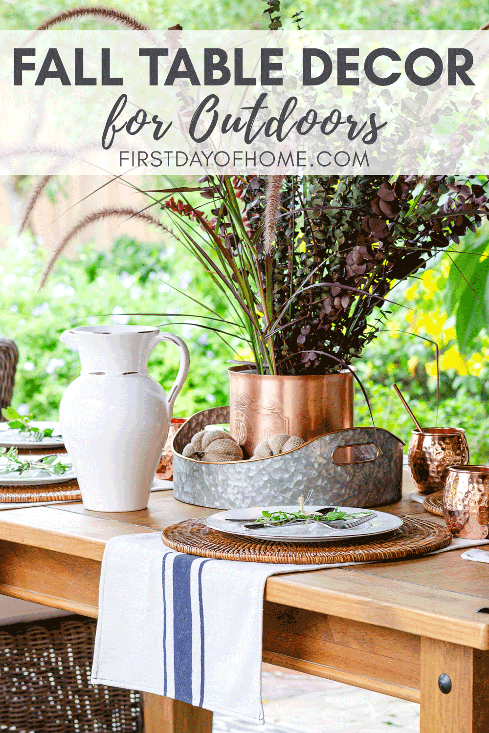 Fall outdoor dining table decor with copper mugs, copper ice bucket, woven placemats and DIY grain sack towels with tall fall centerpiece