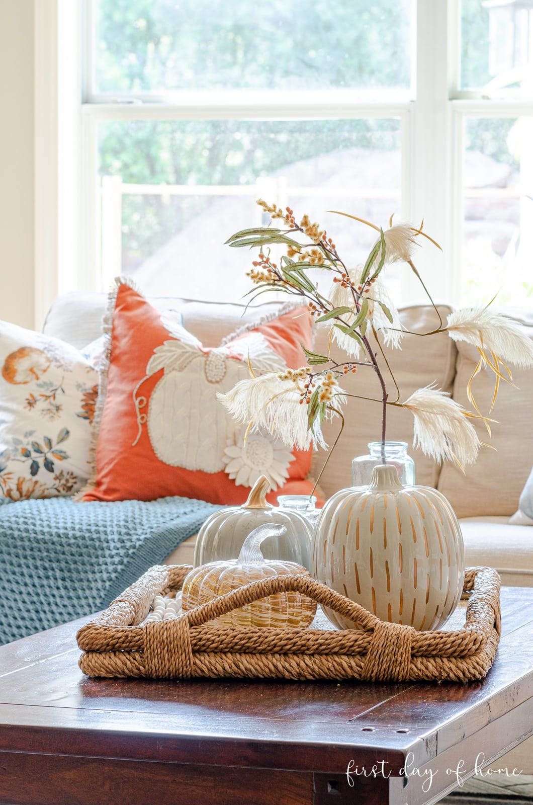 Fall living room tour with pumpkins and stems on coffee table tray and pumpkin throw pillows in background