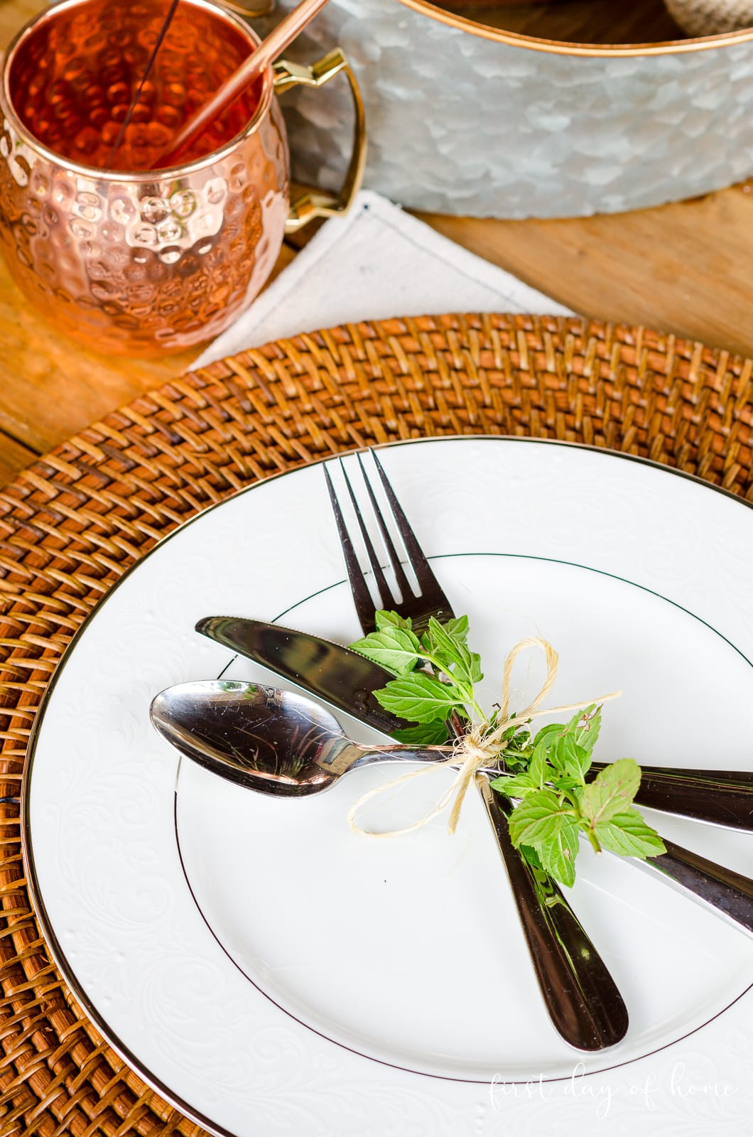 Flatware on fall outdoor tablescape with fresh mint and jute twine on plate