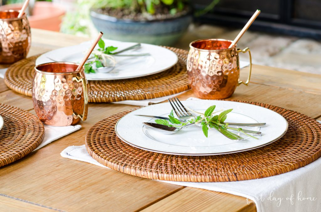 Fall table place setting with woven placemat and copper Moscow Mule mugs
