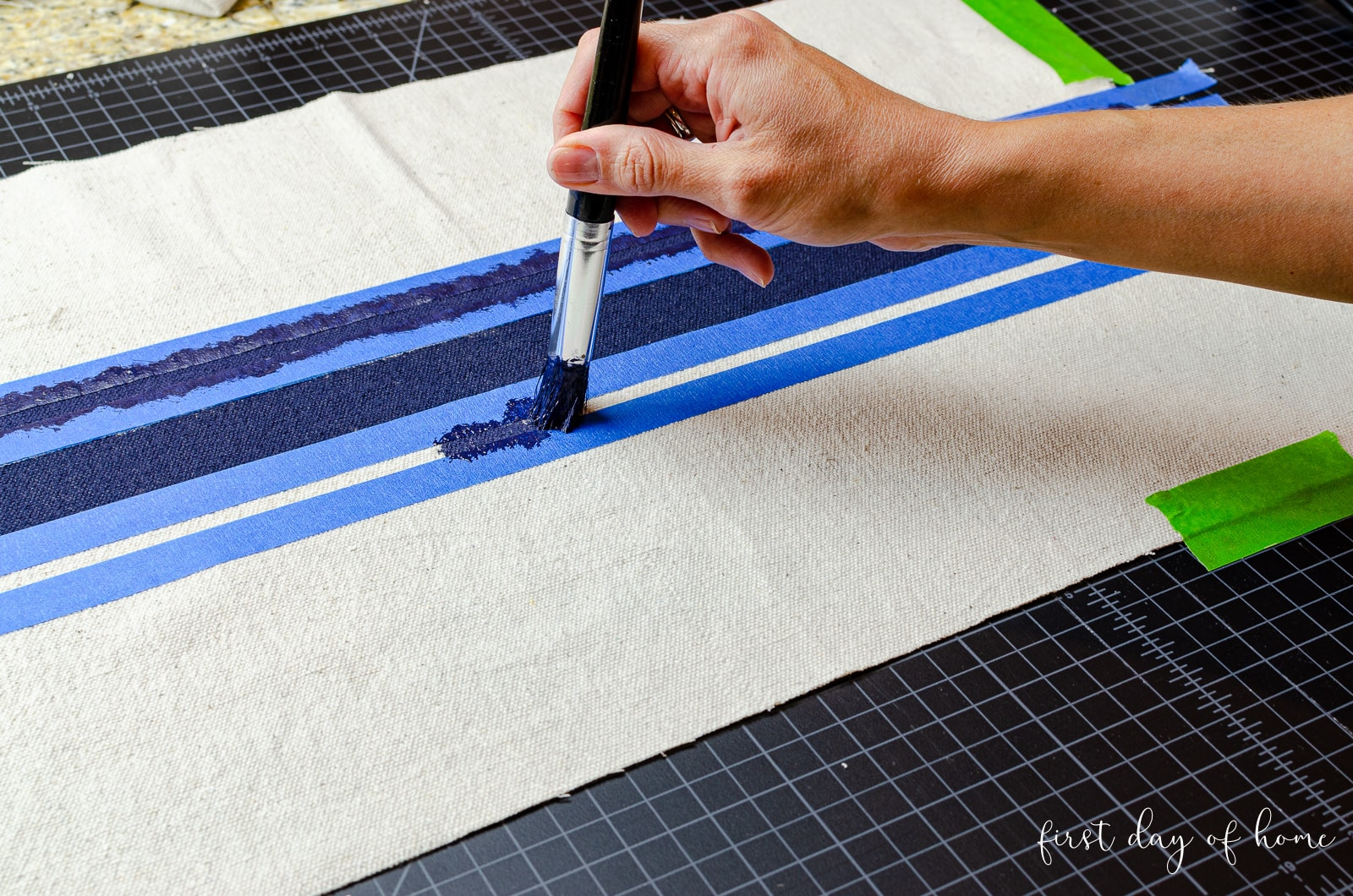 Painting navy stripes on DIY flour sack dish towels made of drop cloth