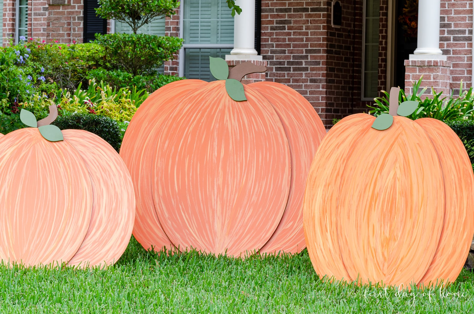 Painted wooden pumpkins on front yard