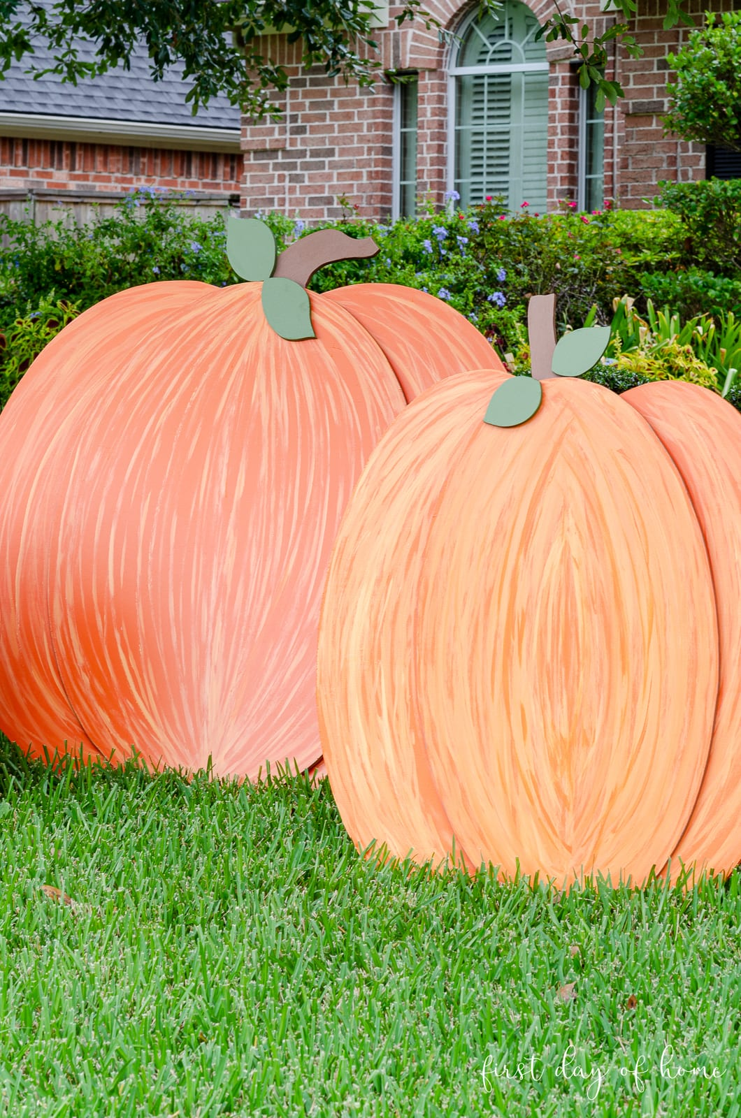 Orange painted wooden pumpkin yard decorations up close