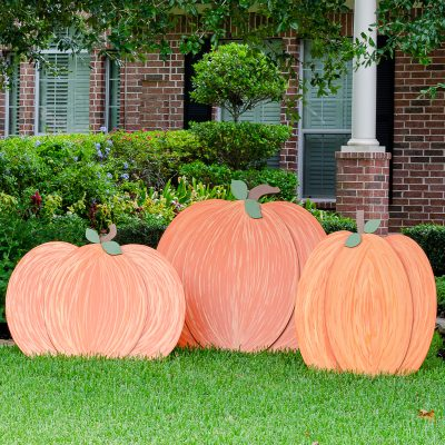 Orange painted wooden pumpkins outdoors on front lawn