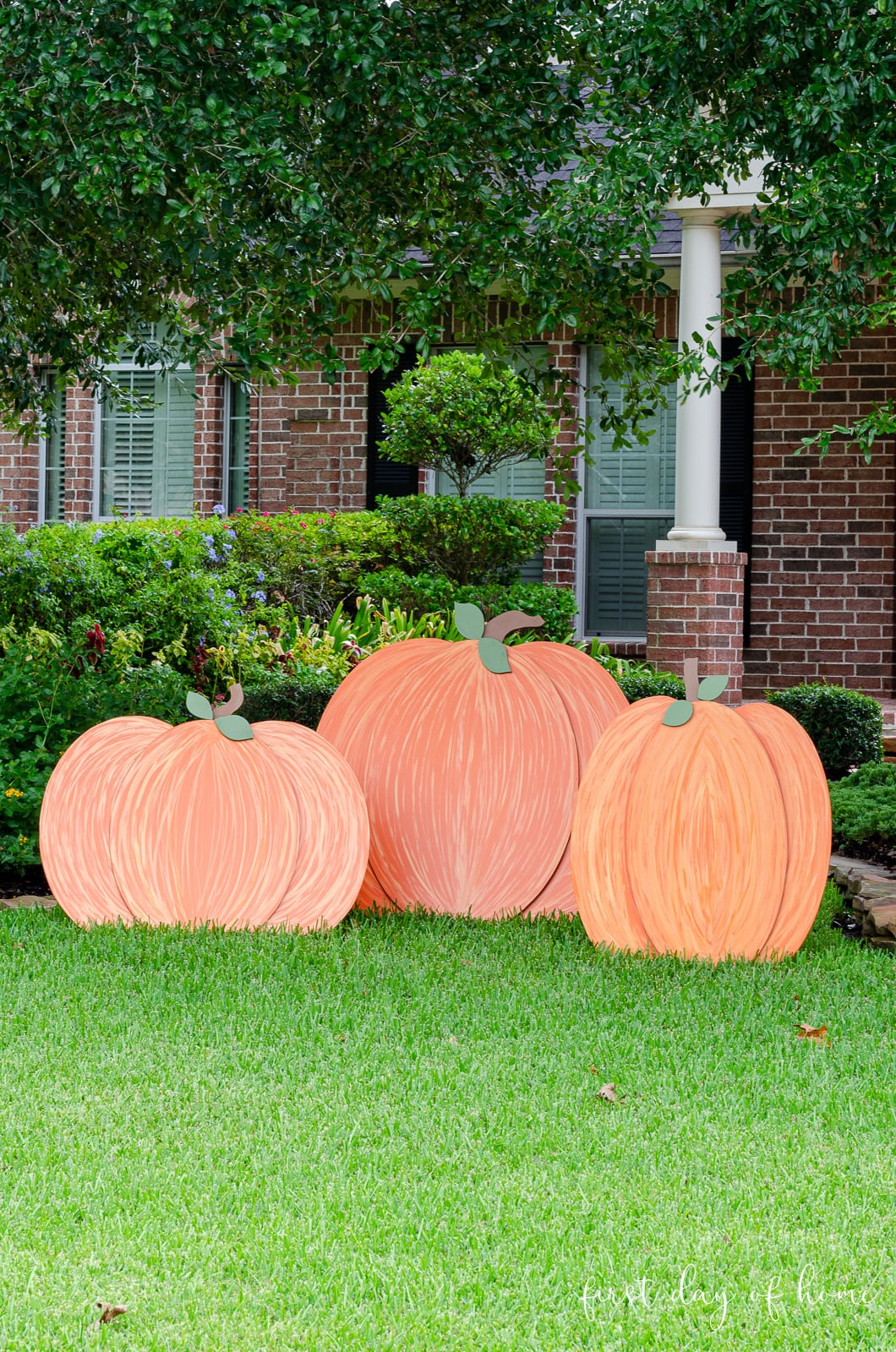 Three orange painted wooden pumpkins sitting on front yard as decorations for fall