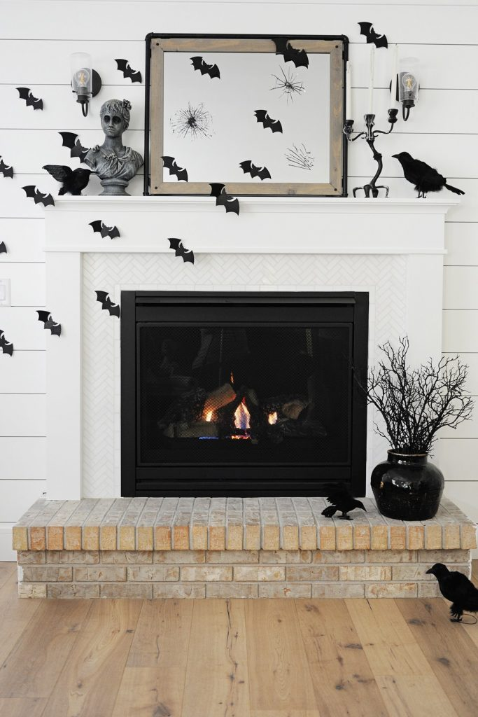 Black and white Halloween mantel decor with bats, birds and broken mirror