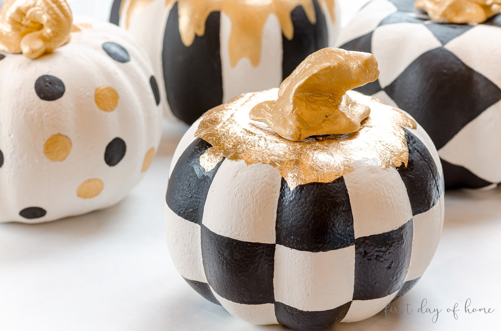 Black and white checkered pattern painted onto foam pumpkin with gold stem