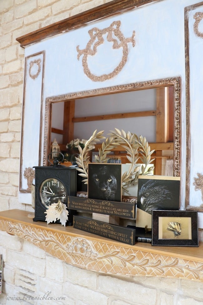 Black and gold Halloween mantel decor with wooden signs and metallic accents