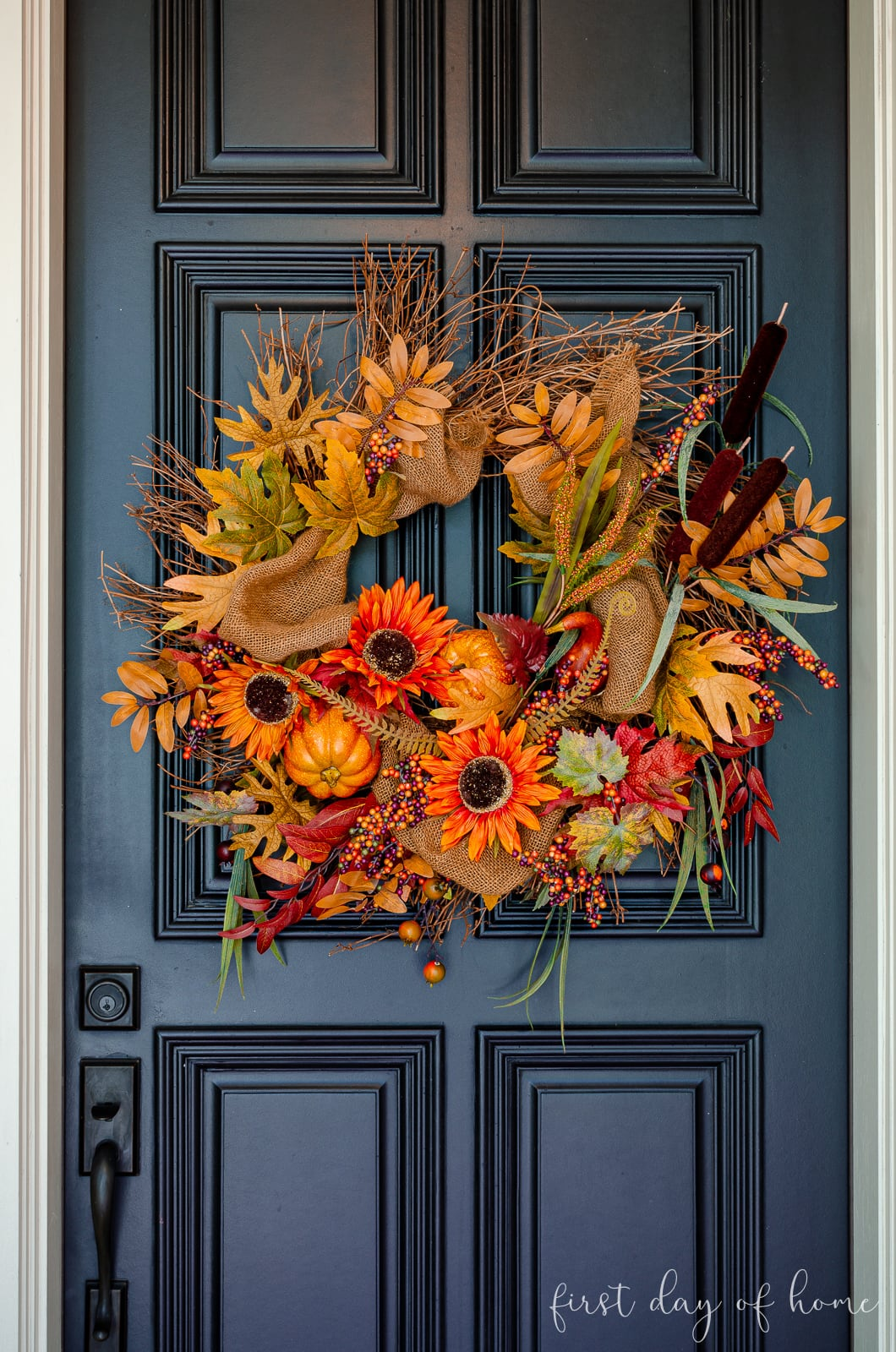 Fall grapevine wreath with leaves, pumpkins and sunflowers hanging on black front door