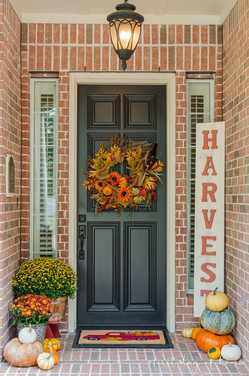 Front porch fall decorating ideas with grapevine wreath on black door, DIY wooden sign, pumpkins, mums and a fall mat