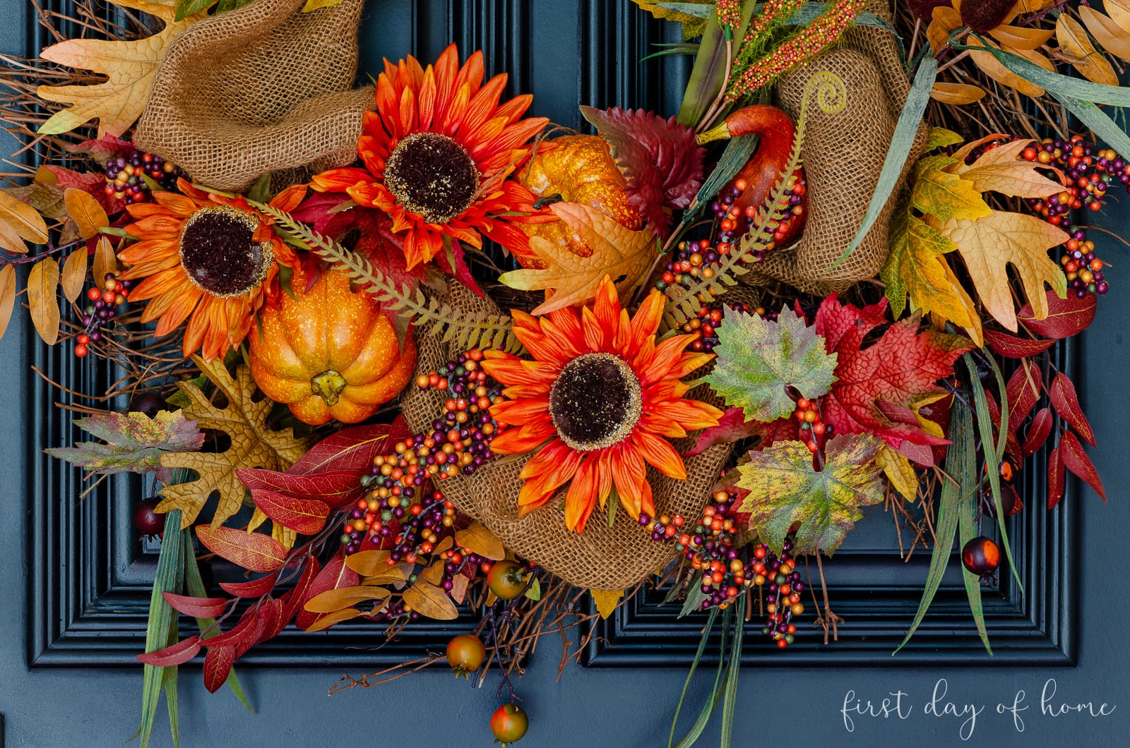Wispy fall grapevine wreath with sunflowers, leaves and pumpkins on black front door