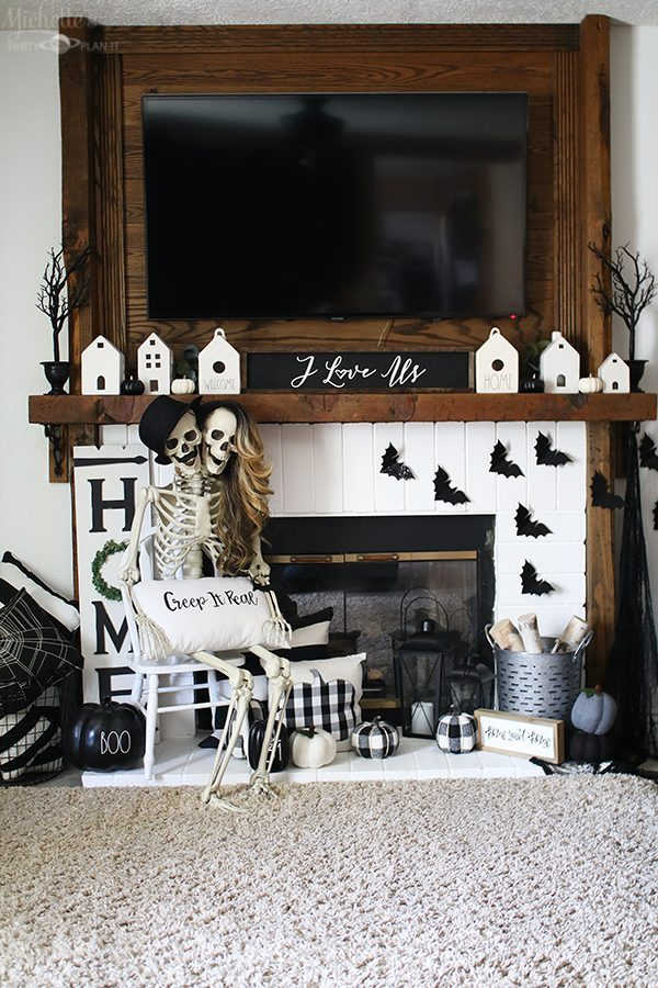 Farmhouse style black and white Halloween mantel with skeletons, pumpkins and bats