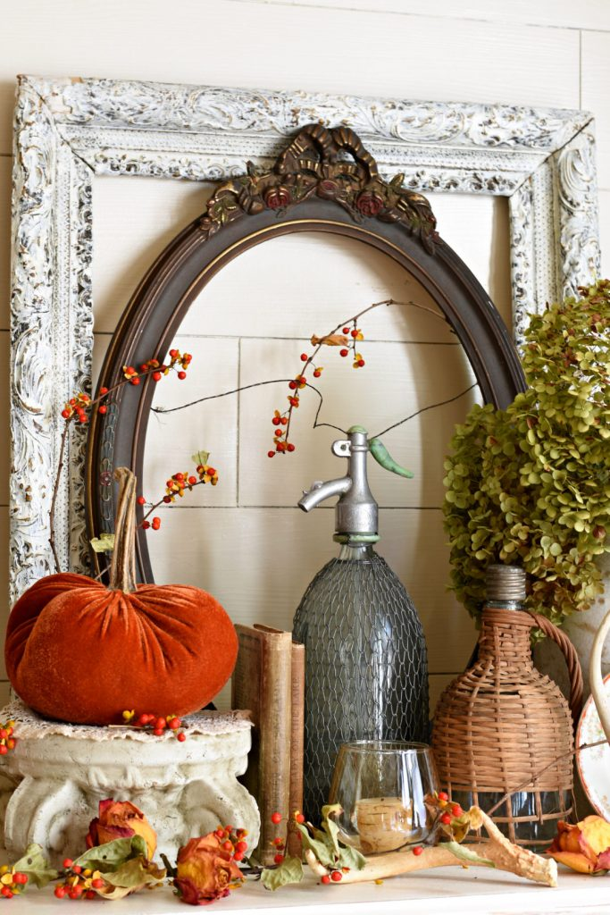 Fall vintage decor vignette with velvet pumpkin and bittersweet accents