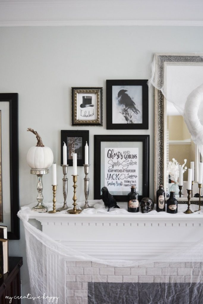Black and white classy Halloween mantel with framed art, mirrors and cheesecloth